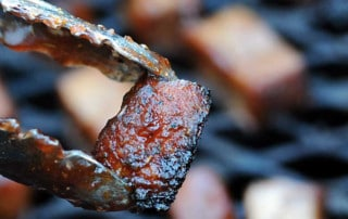 tongs holding smoked turkey burnt ends