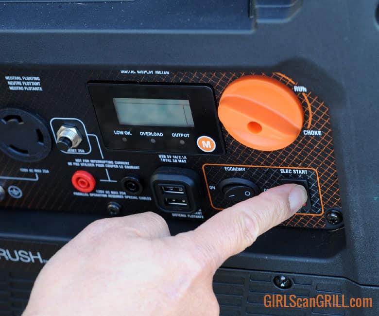 finger pushing electric start on generator panel