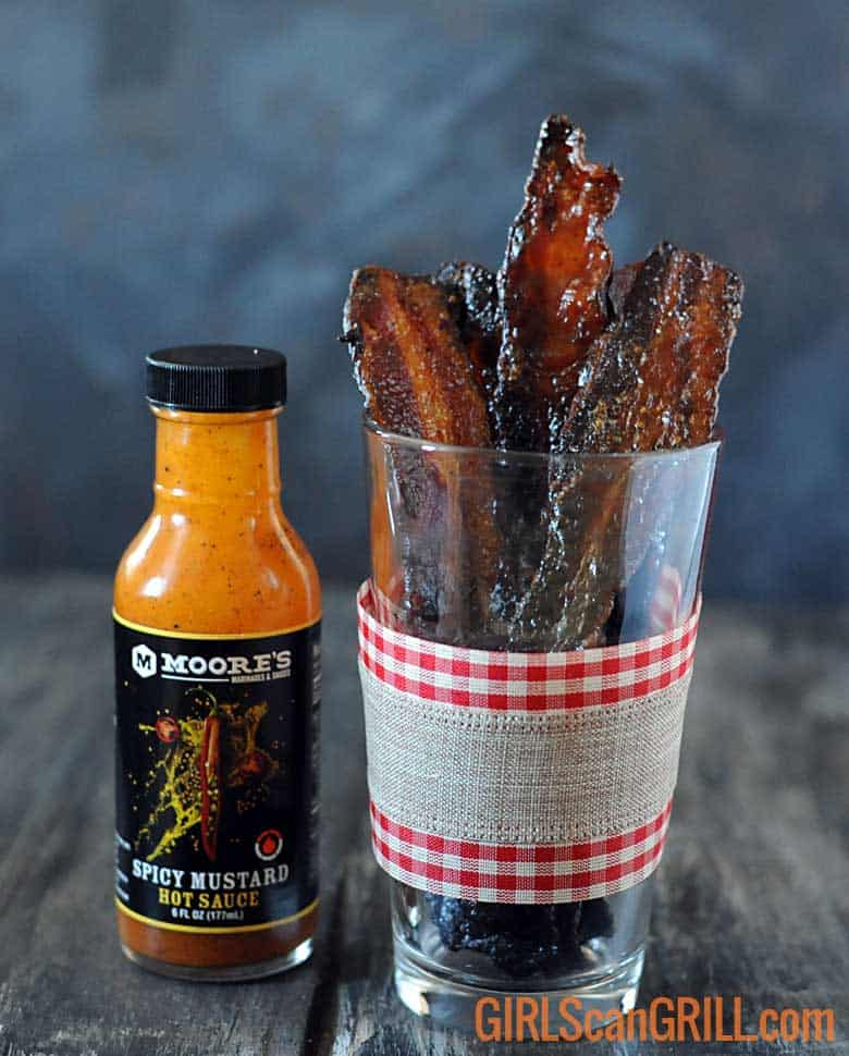 spicy mustard brown sugar bacon in glass with ribbon around it by bottle of hot sauce