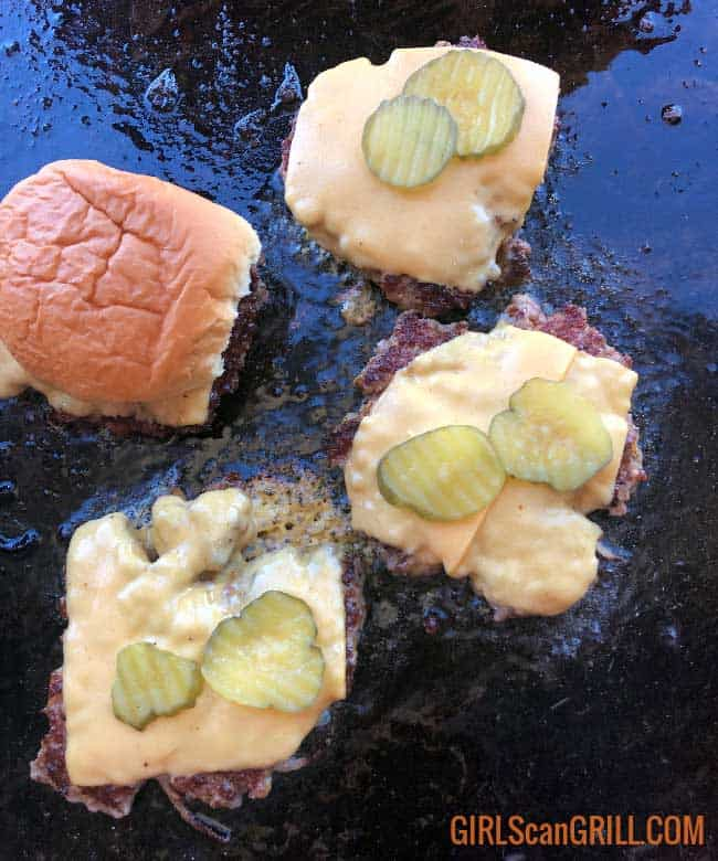 three burger patties on a griddle with cheese and pickles and one bun