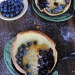 two dutch baby pancake skillets near bowl of blueberries