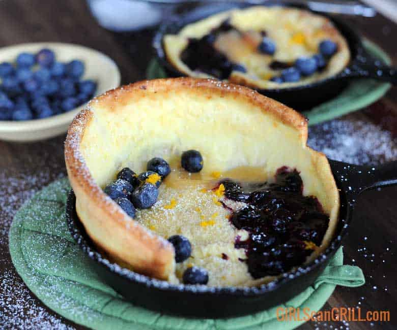 close up of dutch baby pancake with rise in skillet topped with blueberries