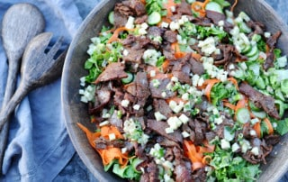 large bowl of beef bulgogi salad with peeled carrots and beef