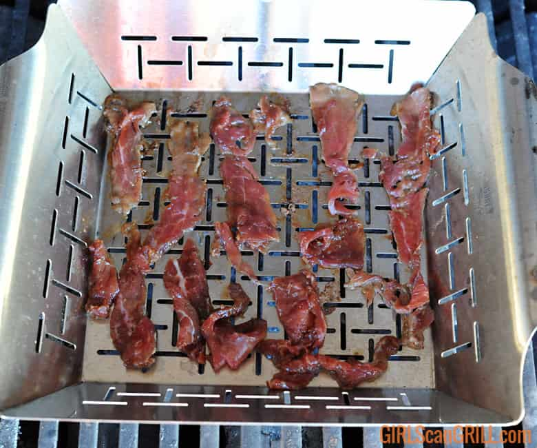 strips of flank steak cooking in a silver veggie basket