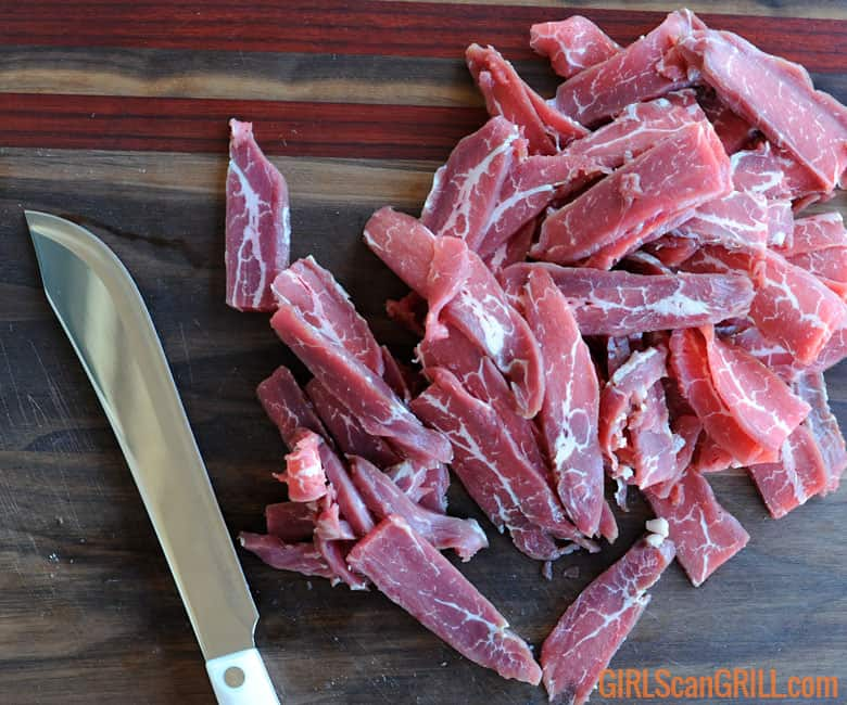 thin slices of raw flank steak on wooden cutting board