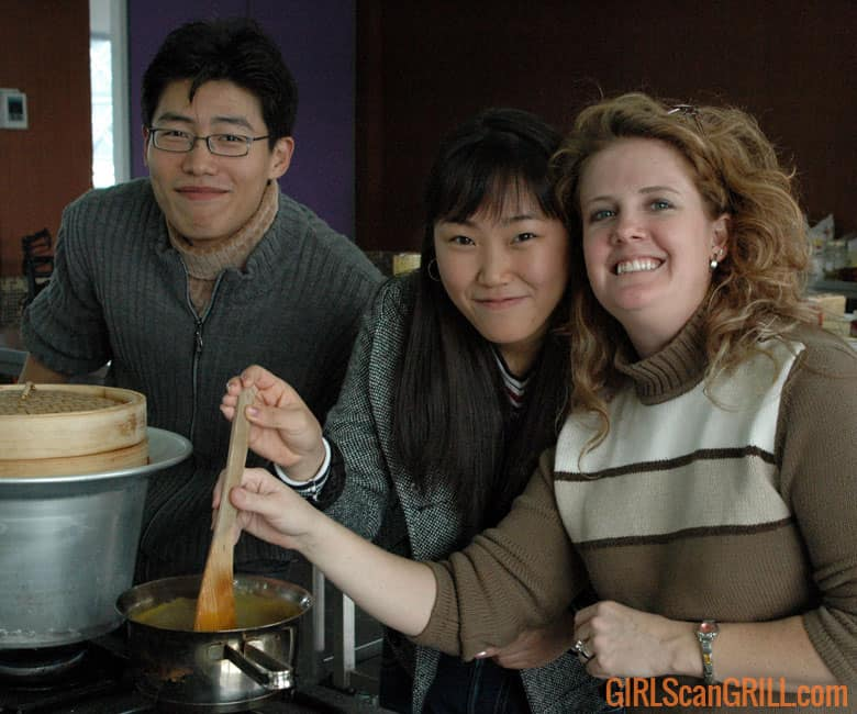 two women holding a spoon, stirring in a pot with a man to their left