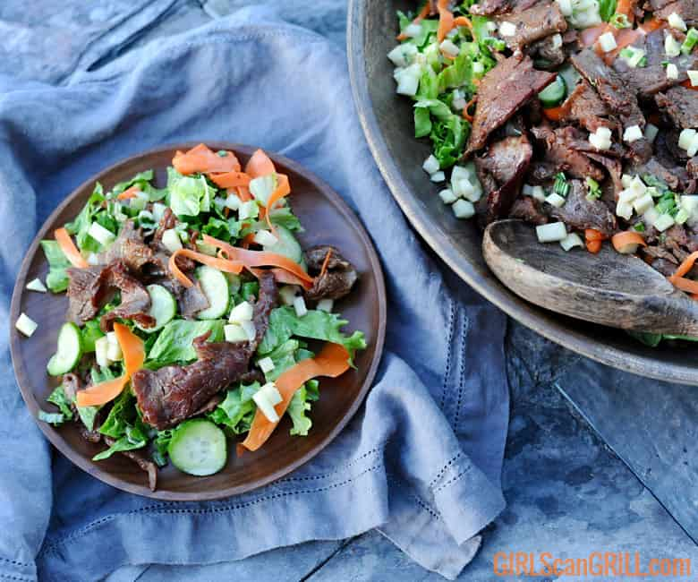large bowl of salad with peeled carrots and beef