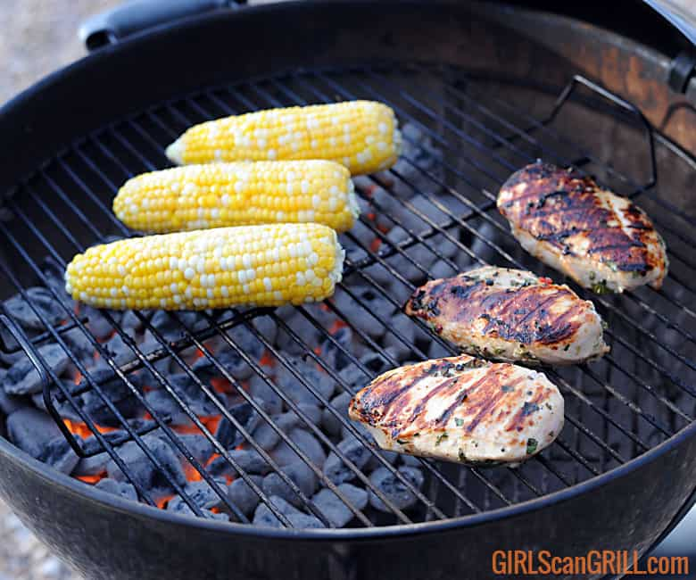the corn cobs on grill to left, three chicken breasts on grill to right