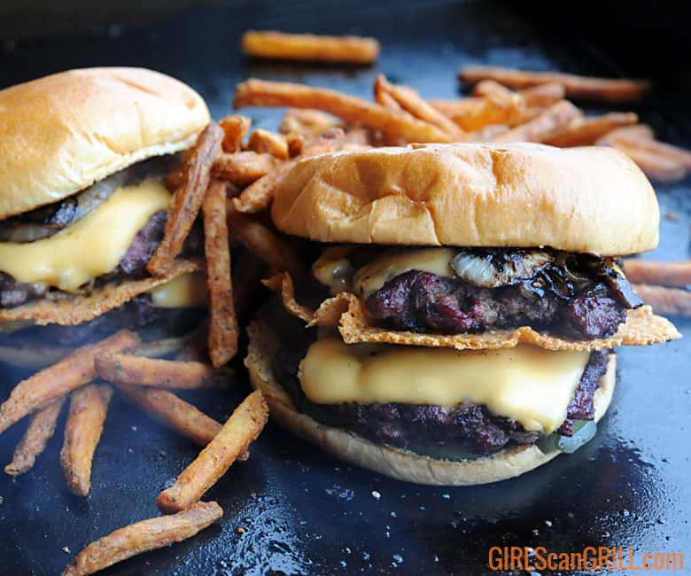 two double smoked smashburger cheeseburgers on a griddle surrounded by fries