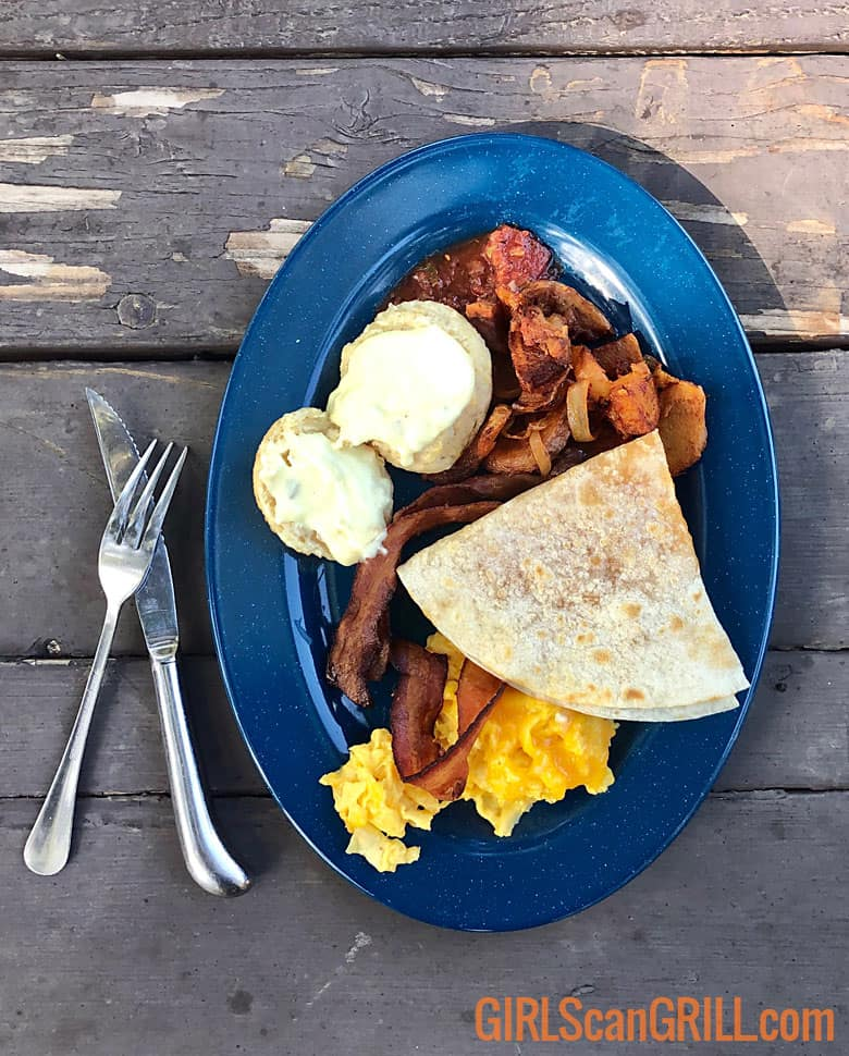 blue plate with eggs, bacon, biscuits and tortilla on a wooden table