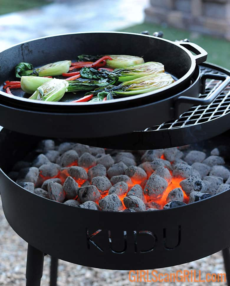 skillet of bok choy searing above bed of coals on KUDU grill