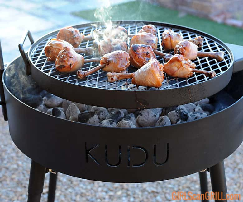 grate of chicken legs cooking above bed of coals on KUDU grill