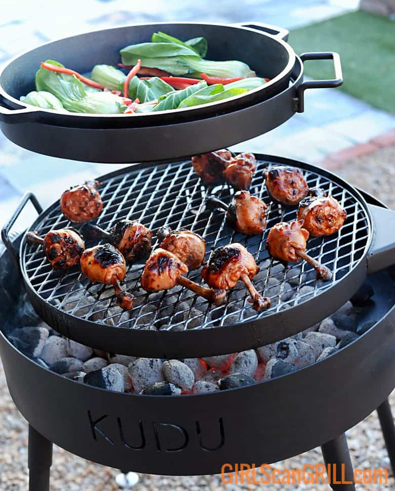 grate of chicken legs and skillet of bok choy searing above bed of coals on KUDU grill