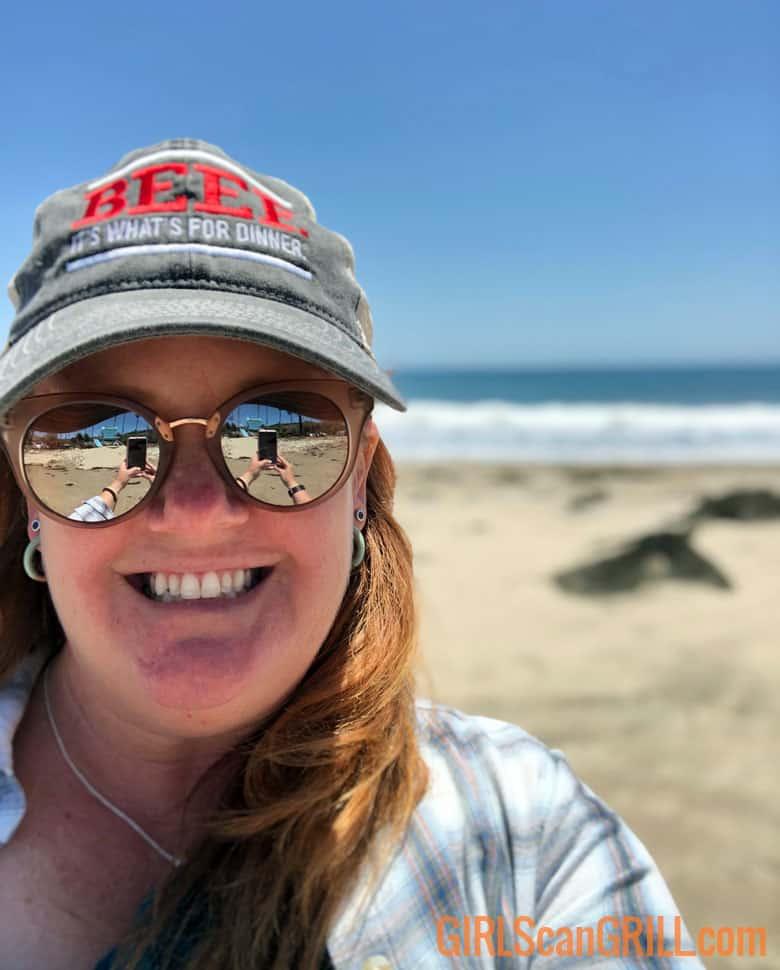 girl in gray hat taking selfie on the beach