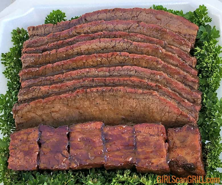 6 brisket burnt ends and 8 brisket slices in box on greens