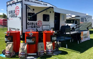 trailer with three orange drum barrels in front with girls can grill logo