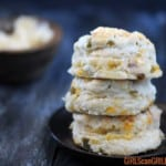 three hatch cheddar biscuits stacked on wooden plate