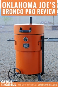 orange Oklahoma Joe's Bronco Pro Drum Smoker in rock backyard