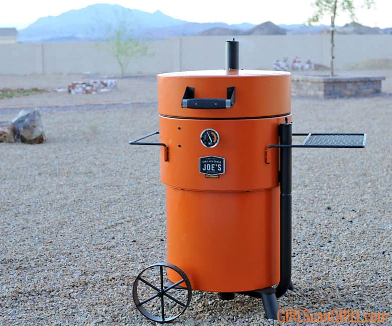 orange Oklahoma Joe's Bronco Pro Drum Smoker in rock backyard