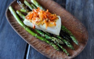 seared sea bass on asparagus topped with carrots