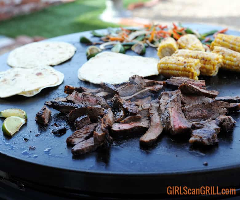 skirt steakon the griddle with corn, tortillas and peppers and onions