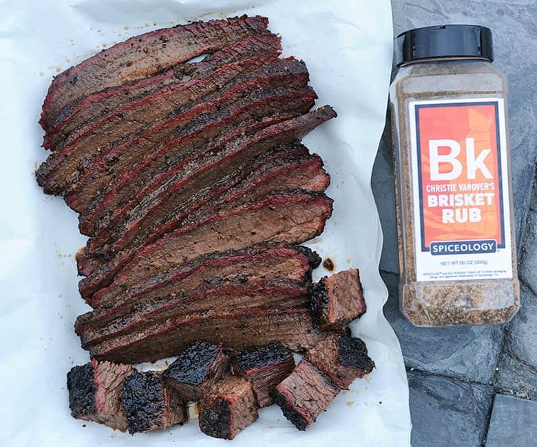 sliced brisket by bottle of BBQ rub