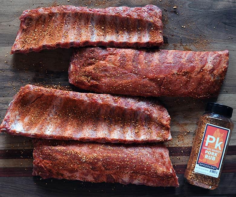 four ribs next to bottle of Pork Rub