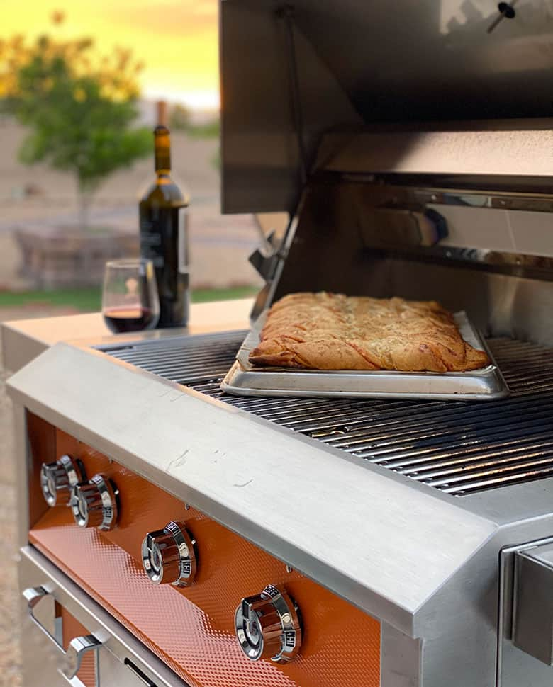 bread baking on grill next to bottle of wine