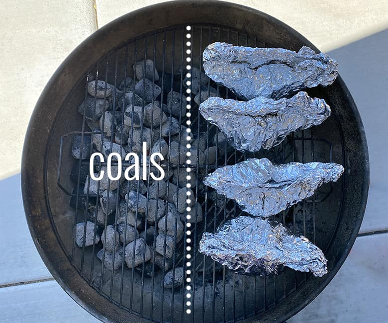 four packets on charcoal grill with coal on left