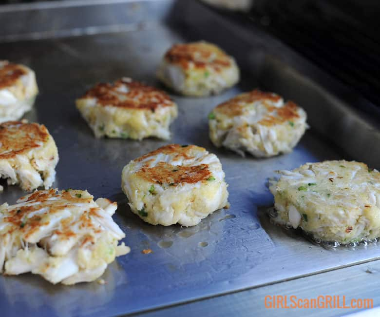 crab cakes cooking on griddle