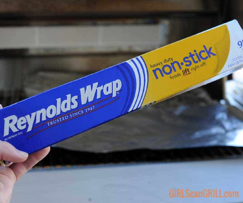 Reynolds Wrap® Non-Stick Aluminum Foil box in front of grill with sheets of foil on grates