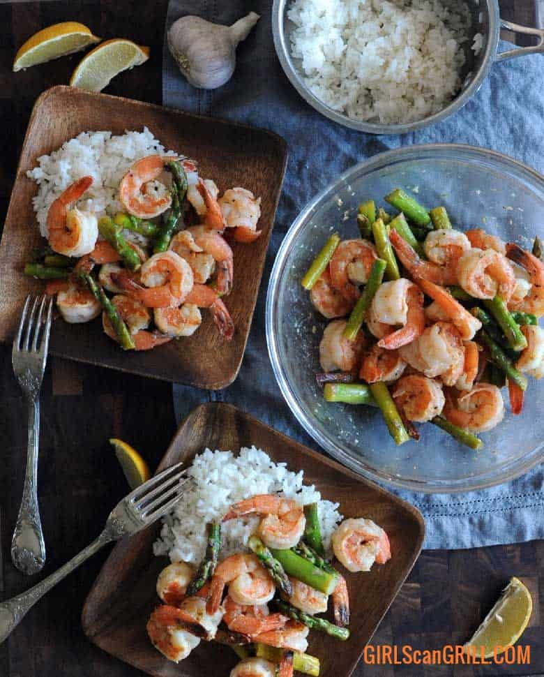 two plates of Lemon Garlic Butter Grilled Shrimp and Asparagus with bowl of shrimp and pot of rice