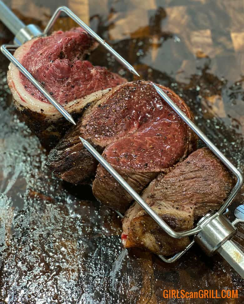 three slices of seared picanha on a spit