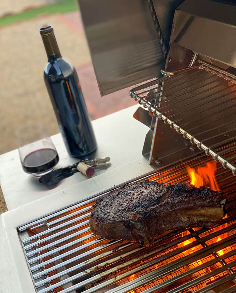steak searing on a grill next to a bottle of wine