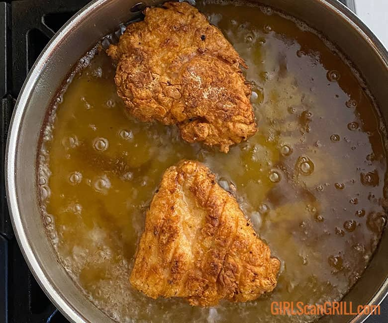 two chicken breasts frying