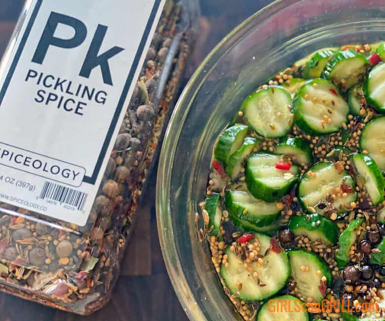 container of pickling spice next to bowl of pickles