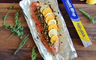 salmon fillet topped with citrus, herbs and nuts on foil
