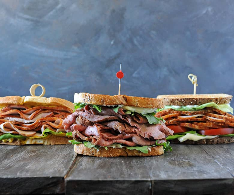 three sandwiches with gray background
