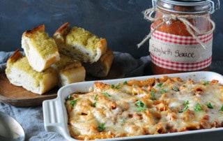 pasta casserole near jar of smoked homemade spaghetti sauce and garlic bread