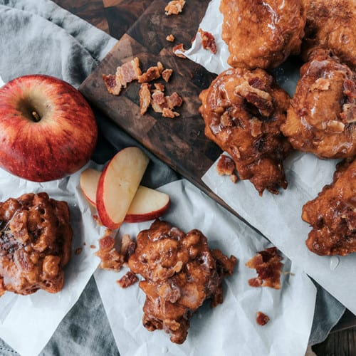 bacon apple fritters stacked on wooden platter