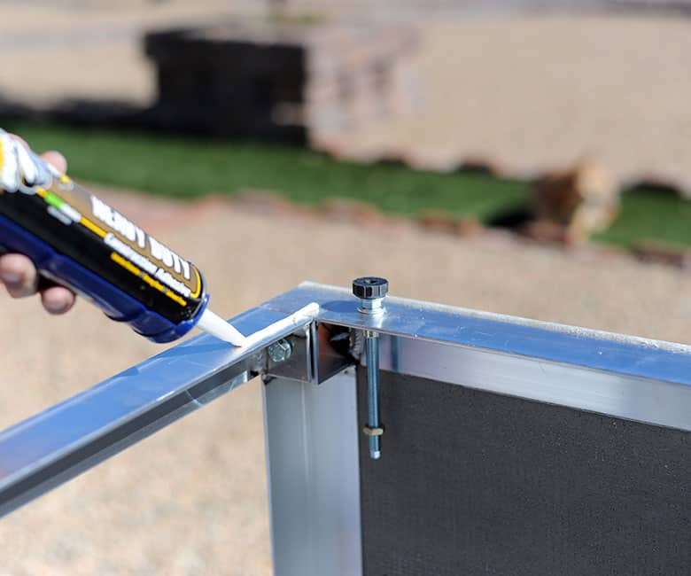 piping adhesive along the metal rail for the bottom