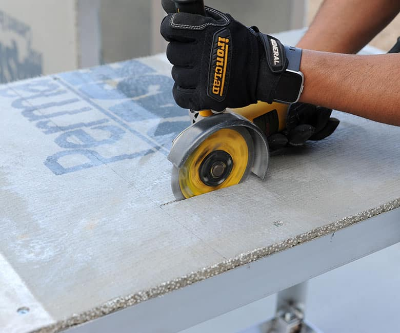 Using an angle grinder to cut a hole in the cement board