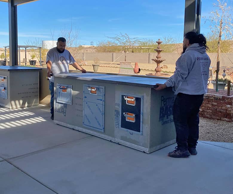 two men adding counters to BBQ island outdoor kitchen