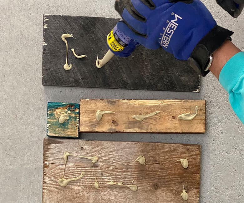 squirting liquid nails onto back of boards