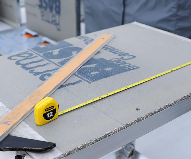 measuring tape and t-square setting on top of BBQ island base