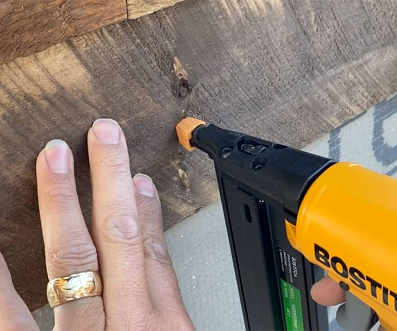 nail gun securing wood to cement board