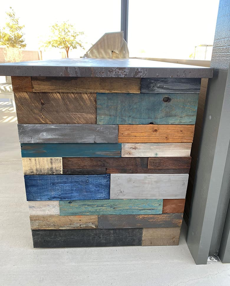 wood planks in gray, blue, brown and white on side of BBQ island