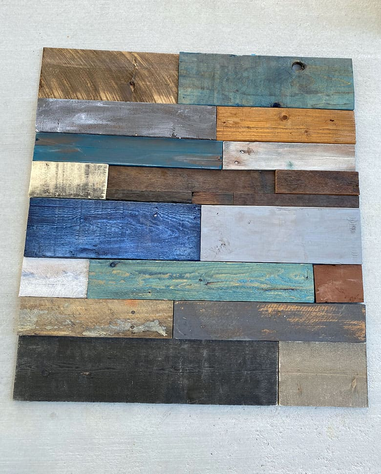 wood planks in gray, blue, brown and white laid out on the ground