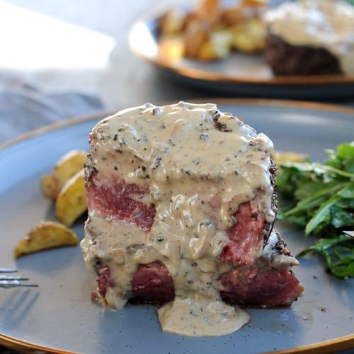 medium rare filet mignon cut in half with peppercorn sauce