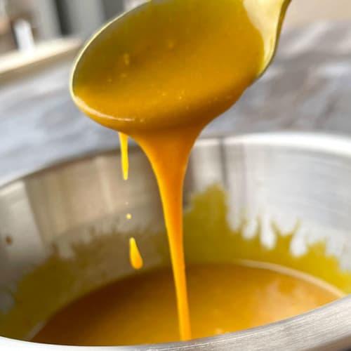 spoon dripping carolina mustard bbq sauce into bowl